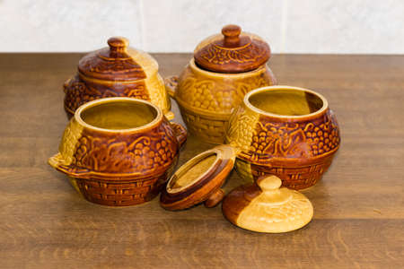Set of the four empty glazed clay pots for cooking with lids on a cook table with selective focus