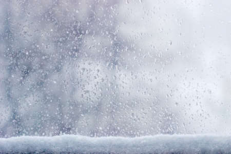 Background of the streams and drops of water on the window pane with accumulation of wet snow at the bottom of window during a snowfall  Reklamní fotografie