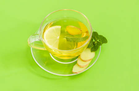 Tea with slices of fresh ginger, lemon and mint leaf in the glass transparent cup on a glass saucer with mint twig and fresh ginger root slices on a green background