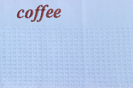 Fragment of the blue waffle kitchen towel with brown word coffee 版權商用圖片