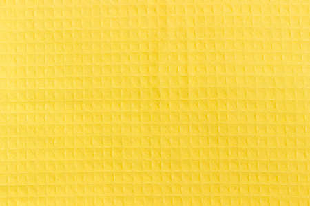 Background of a surface of the yellow waffle towel with horizontal layout of pattern