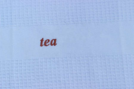 Fragment of the blue waffle kitchen towel with brown word tea