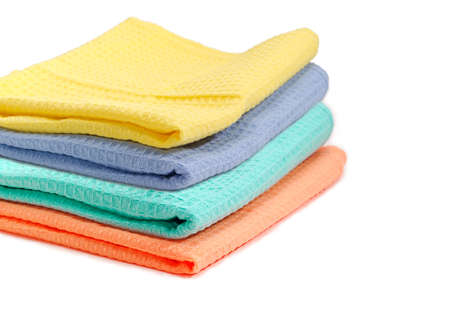 Set of multicolored folded waffle towels piled on in stack closeup with selective focus on a white background  Stock Photo