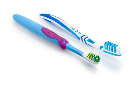 Traditional blue and white toothbrush and blue standard electric toothbrush with rotating and oscillating brushes and rechargeable battery on a white matte surface on a white background Banco de Imagens - 94939532