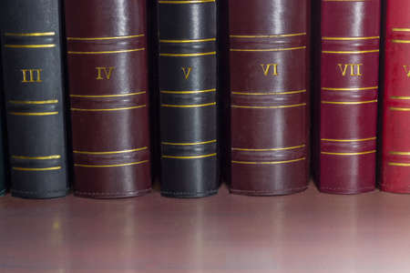 Fragment of several black, cerise and red book spines of the old tomes of the collected works in leather-bound on the shelf