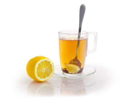Glass cup of black tea with petals of flowers and lemon slice, spoon in it on a glass saucer and lemon beside on a matte surface on a white background Banco de Imagens - 96724454