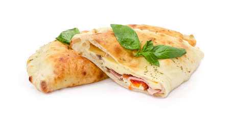Half of the baked calzone on background of whole calzone - closed type of pizza that is folded in half, decorated with basil twigs on a white background