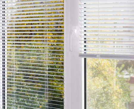 Inside view of part of the modern plastic window with white Venetian blinds, partly raised on one half of the window with mosquito net and blurred view of foliage across window  Reklamní fotografie