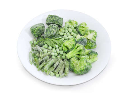 Various frozen green vegetables - green beans, broccoli, cubes of chopped spinach and green peas covered with rime, twig of fresh parsley on the white dish on a white background  Standard-Bild