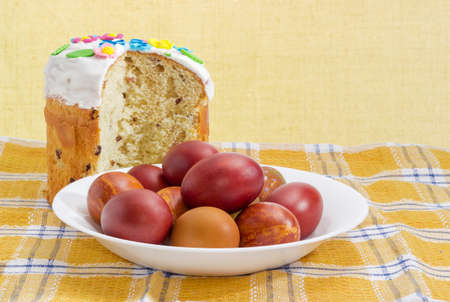 Partly cut Easter cake decorated with white icing and colorful sugar decors, dish with Easter eggs on the checkered tablecloth