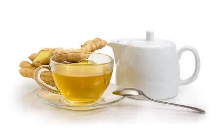 Ginger tea in the glass transparent cup on a glass saucer with tea spoon, white porcellaneous teapot and fresh ginger roots on a white background