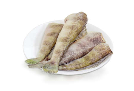 Several uncooked carcasses of the notothenia fish without of the heads on a white dish on a white background  Stock Photo