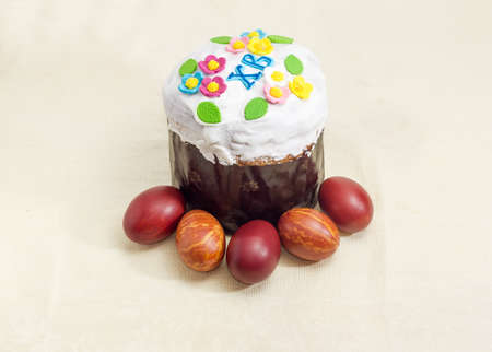 Easter cake decorated with white icing and colorful sugar decors, wrapped in special parchment baking paper and Easter eggs on the tablecloth  Stock Photo