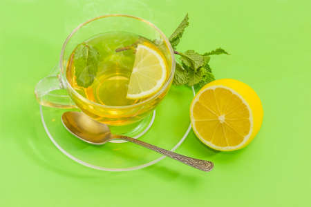 Tea with slice of fresh lemon and mint leaf in the glass transparent cup on a glass saucer with tea spoon and mint twig, half of lemon beside on a green background
