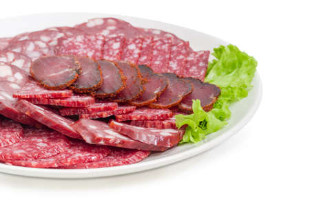 Fragment of the white dish with sliced two different salami, smoked sausage and dried pork tenderloin on lettuce leaf closeup at selective focus on a white background