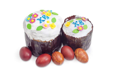 Two Easter cakes different sizes decorated with white icing and colorful sugar decors, wrapped in special parchment baking paper and Easter eggs on a white background