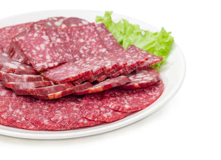 Fragment of the white dish with sliced two different salami and smoked sausage on lettuce leaf closeup at selective focus on a white background
