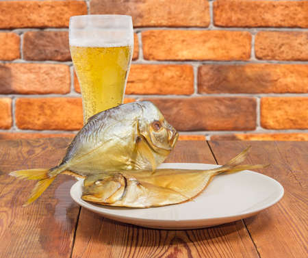 Two smoked Selene setapinnis, also known as Atlantic moonfish, on a white dish and the glass of lager beer on the old rustic table against of a brick wall