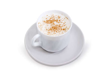 Coffee with foamed cream sprinkled with cinnamon powder in the white cup on the saucer on a white background