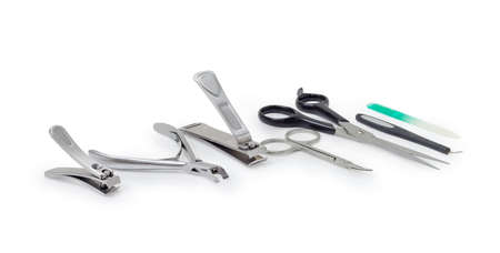 Different scissors, nail clippers and other hand tools for nail care at selective focus on a white background