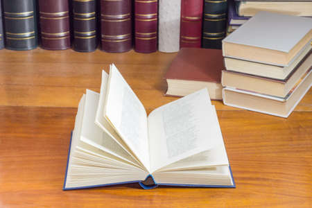 Open book with blue hardback on a wooden table at shallow depth of field with blurred text against of the other books on the background
