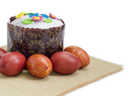 Fragment of the cloth napkin and Easter cake decorated with white icing and colorful sugar decors, wrapped in special parchment baking paper and Easter eggs on it on a white background