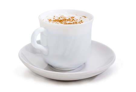 Coffee with foamed cream sprinkled with cinnamon powder in the white cup on the saucer closeup at selective focus on a white background  Stock Photo