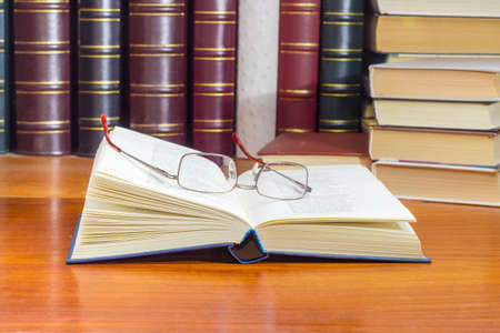 Open book in blue hardcover and classic mens eyeglasses on it on a wooden table at selective focus with blurred text against of the other books on the background