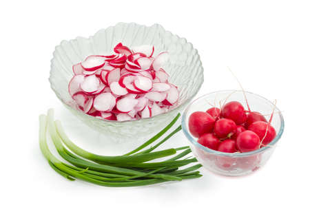 Green onion, sliced red radish in salad bowl and whole washed red round radishes in glass bowl - basic ingredients for the vegetable salad preparation on a white background  Stock Photo