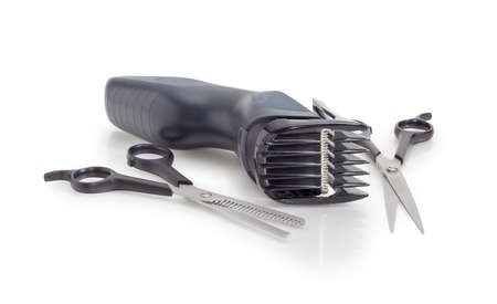 Electric hair clipper with nozzle for cutting height adjustment, thinning shears and normal hairdressers scissors on matte surface on a white background