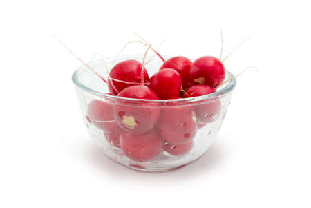 Fresh washed red round radishes without haulm in the transparent glass bowl on a white background