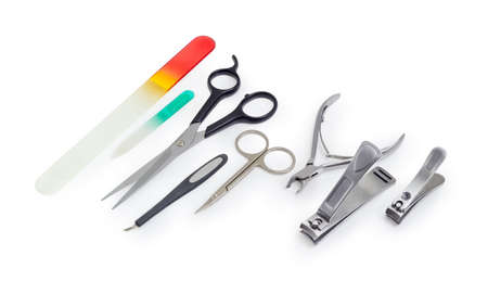 Different scissors, nail clippers, nail files and other hand tools for nail care on a white background