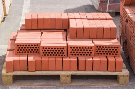 Red perforated building bricks with round holes on wooden pallet on an outdoor warehouse in sunny day