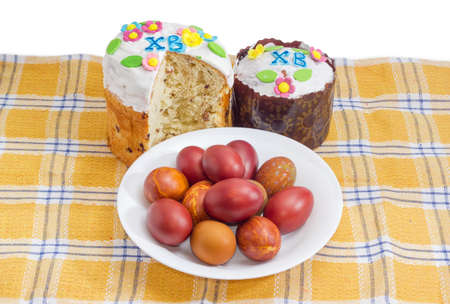 One whole and one partly cut Easter cakes decorated with white icing and colorful sugar decors, dish with Easter eggs on checkered tablecloth on a white background