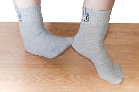 Legs of woman in the light gray socks for fitness on a wooden floor at selective focus on a white background