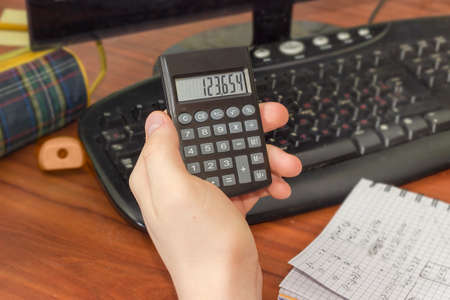 Modern electronic pocket calculator with a liquid-crystal display in the hand of schoolboy over the desktop