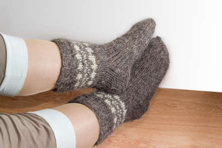 Pair of the thick gray wool hand-knitted socks on women legs on the wooden floor on a light colored background  Stock Photo