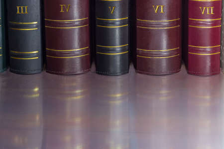 Fragment of several black, cerise and red book spines of the old tomes in leather-bound on the shelf