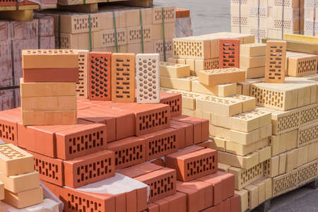 Perforated building bricks of different colors and shapes of holes on a pallets on an outdoor warehouse in sunny day  Stock Photo