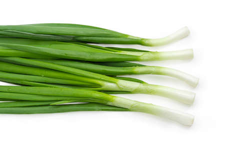 Top view of the several washed and peeled stalks of the green onion with drops of water on a white background