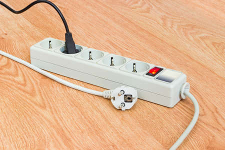 Power strip with electrical sockets of CEE 7 standard, one mains cables connected to it and one unconnected cable beside on a wooden surface