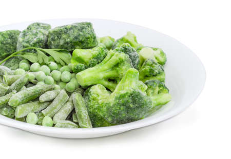 Fragment of white dish with various frozen green vegetables - green beans, broccoli, cubes of chopped spinach and green peas covered with rime at selective focus on a white background   Stock Photo