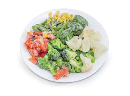 Frozen cut green beans, broccoli, cauliflower, cubes of chopped spinach, sweet corn kernels, chopped bell pepper and green peas covered with rime on white dish on a white background   Stock Photo