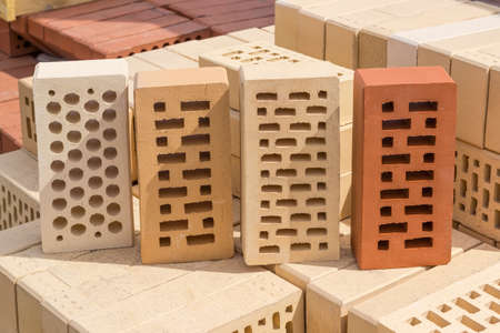 Several perforated bricks of different colors and shapes of holes on a pallet with other bricks on an outdoor warehouse in sunny day