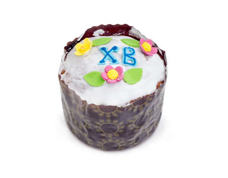 Easter cake decorated with white icing and colorful sugar decors, wrapped in special parchment baking paper on a white background