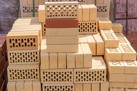 Yellow perforated bricks with rectangular holes on pallet among of other bricks on an outdoor warehouse in sunny day