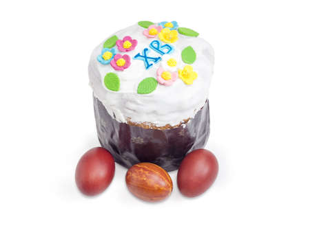Easter cake decorated with white icing and colorful sugar decors, wrapped in special parchment baking paper and Easter eggs on a white background  Stock Photo