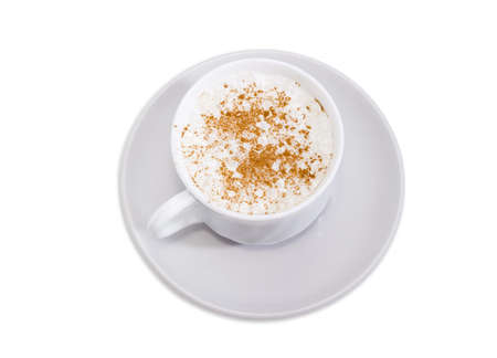 Top view of coffee with foamed cream sprinkled with cinnamon powder in the white cup on the saucer on a white background  Stock Photo