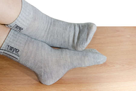 Light gray socks for fitness on the legs of woman on a wooden floor closeup on a white background
