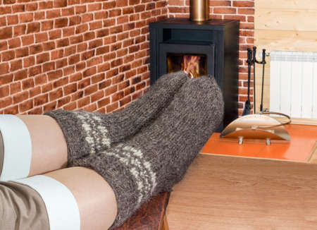 Pair of the thick gray wool hand-knitted socks on women legs on the background of a burning fireplace